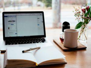 mesa com notebook, xícara e um caderno