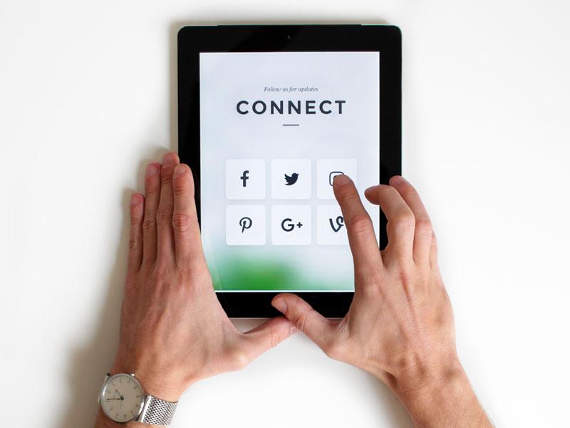 homem usando tablet com redes sociais