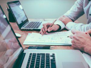 dois homens se reunindo e apontando para papel ao lado de dois notebooks