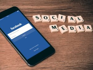 celular com a tela do facebook aberto e peças escrito social media
