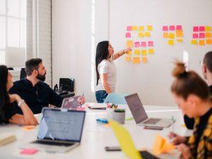sala de reunião com post-it em lousa e notebooks na mesa