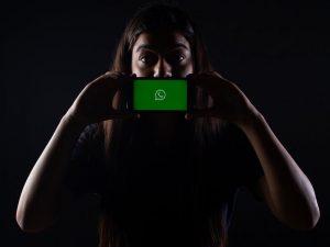 mulher com celular com a logotipo do whatsapp cobrindo a boca